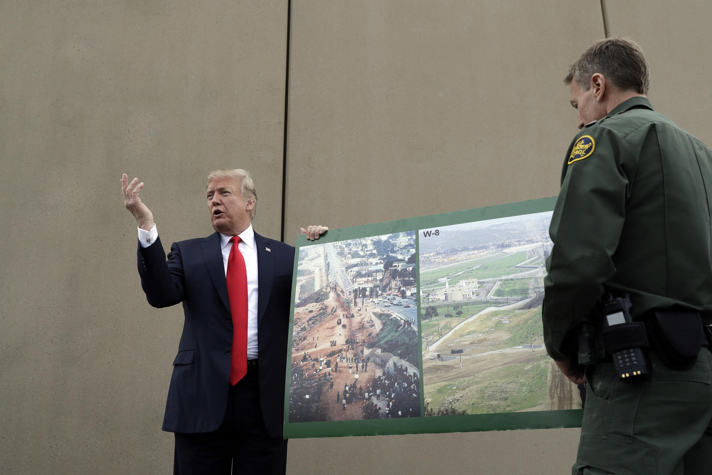 President Donald Trump holds a photo of the border area (Evan Vucci/AP)