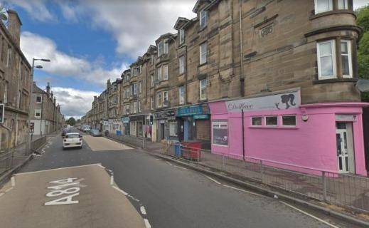 The man was found behind shops in Glasgow Road